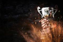 拿着在黑暗的背景的一个人的低调图象一个战利品杯子 库存照片