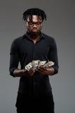 拿着在黑暗的背景的年轻成功的非洲商人金钱 库存照片