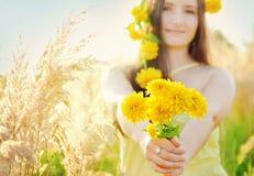 拿着在晴朗的夏天草地的俏丽的女孩花束 图库摄影