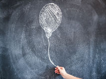 拿着在黑板的女性手一个拉长的气球 库存图片