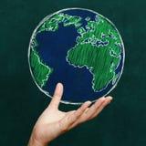 拿着在黑板的手世界 免版税库存图片