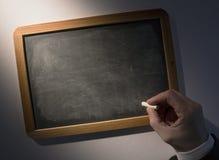 拿着在黑板的手白垩 免版税库存照片
