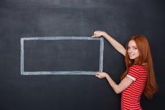 拿着在黑板背景的愉快的妇女被画的框架 免版税库存图片