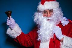 拿着在他的右手的圣诞老人响铃 库存图片