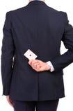 拿着在他的后的商人纸牌。 免版税图库摄影