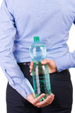 拿着在他的后的商人绿色瓶。 免版税库存照片