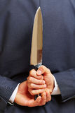 拿着在他的后的手刀子  免版税库存照片
