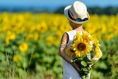拿着在他的后面后的帽子的可爱的男孩向日葵在黄色领域蓝天户外 免版税库存图片