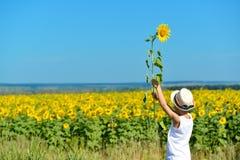 拿着在他的后面后的帽子的可爱的男孩向日葵在黄色领域蓝天户外 库存照片