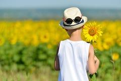 拿着在他的后面后的帽子的可爱的男孩向日葵在黄色领域蓝天户外 库存图片