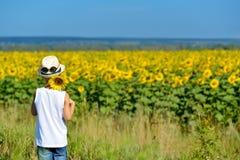 拿着在他的后面后的帽子的可爱的男孩向日葵在黄色领域蓝天户外 免版税图库摄影