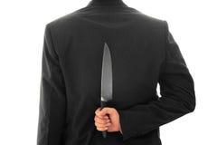 拿着在他的后面概念性图象后的商人刀子被隔绝 免版税库存图片