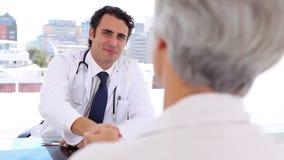 拿着在他的患者前面的微笑的医生一个X-射线 影视素材