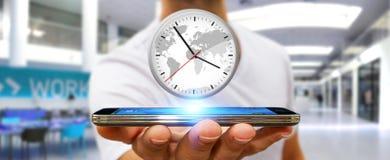 拿着在他的手机的商人一个时钟 库存图片