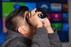 拿着在他的眼睛的年轻亚裔人虚拟现实风镜 免版税库存照片