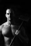 拿着在他的肩膀的运动人一把锤子 免版税库存照片