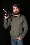 拿着在他的胳膊的有胡子的人照相机 关闭 黑色背景 免版税库存照片