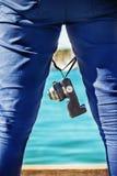 拿着在他的腿和身分之间的人一台照片照相机近 库存照片