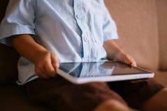 拿着在他的膝部的小男孩一种片剂 免版税库存图片