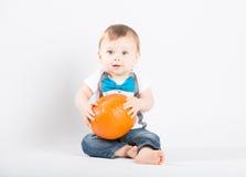 拿着在他的膝部的婴孩南瓜 免版税库存图片