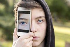 拿着在他的面孔前面的十几岁的男孩一个巧妙的电话 免版税图库摄影