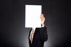 拿着在他的面孔前面的商人一张纸 免版税库存图片