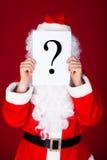 拿着在他的面孔前面的圣诞老人问号 库存图片