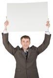 拿着在他的头上的商人白纸 免版税库存图片