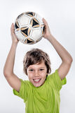 拿着在他的头上的逗人喜爱的微笑的足球孩子球 库存照片