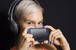 拿着在嘴的年轻可爱的网络女孩特写镜头智能手机 免版税库存照片