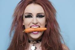 拿着在嘴的质朴的少妇画象红萝卜在蓝色背景 免版税图库摄影