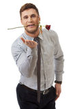 拿着在他的嘴的英俊的人红色玫瑰 免版税库存照片