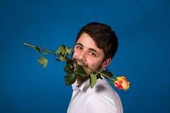 拿着在他的嘴的年轻人一朵红色玫瑰 库存图片