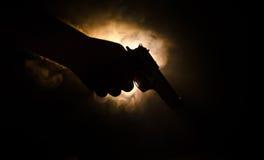拿着在黑背景的男性手枪与烟(橙黄红色白色)上色了后面光,黑手党凶手概念 免版税库存照片