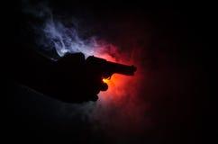 拿着在黑背景的男性手枪与烟(橙黄红色白色)上色了后面光,黑手党凶手概念 库存照片
