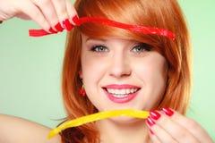 拿着在绿色的Redhair女孩甜食物果冻糖果 库存照片