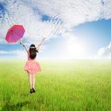 拿着在绿色米的愉快的妇女伞在太阳天空调遣 图库摄影