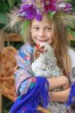 拿着在绿色背景的女孩一只公鸡 库存图片