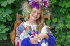 拿着在绿色背景的女孩一只公鸡 免版税库存照片