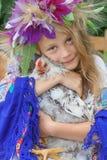 拿着在绿色背景的女孩一只公鸡 库存照片