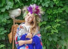 拿着在绿色背景的女孩一只公鸡 免版税库存图片