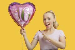 拿着在黄色背景的惊奇的少妇画象心形的生日气球 库存图片