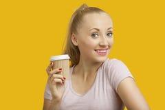 拿着在黄色背景的美丽的少妇画象一次性杯子 免版税图库摄影