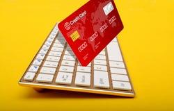 拿着在黄色背景的键盘键一张信用卡 免版税库存图片