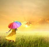拿着在绿草领域和日落的美丽的妇女多彩多姿的伞 免版税库存图片