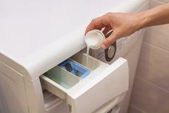 拿着在洗衣机的手织品软化剂 库存照片