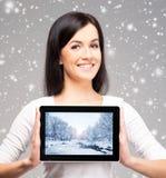 拿着在h的年轻和美丽的少年女孩一台ipad片剂个人计算机 库存图片