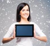 拿着在h的年轻和美丽的少年女孩一台ipad片剂个人计算机 免版税库存照片