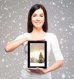 拿着在h的年轻和美丽的少年女孩一台ipad片剂个人计算机 图库摄影