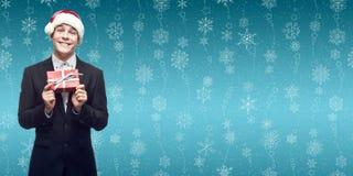 拿着在wint的圣诞老人帽子的年轻商人圣诞节礼物 免版税图库摄影